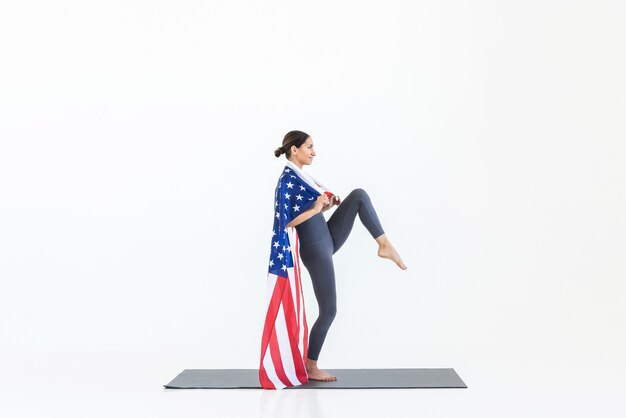 Gelukkige jonge amerikaanse vrouw met usa-vlag beoefent yoga terwijl ze op een mat op een witte scène staat. 4 juli onafhankelijkheidsdag concept