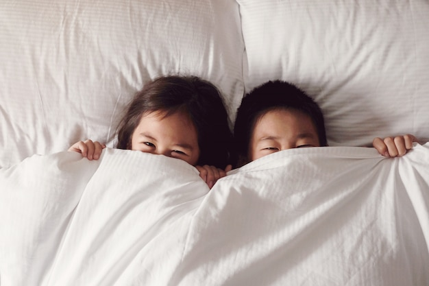 Gelukkige jonge aziatische broer en zus die hun gezichten bedekken met deken en 's ochtends vrolijk gluren