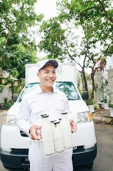 Gelukkige jonge aziatische leveringsmens die draadkraan met melkflessen aan klant draagt