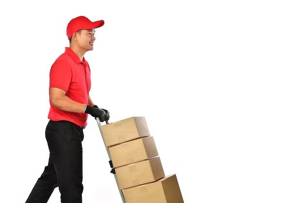 Gelukkige jonge aziatische leveringsmens die in rood uniform een steekwagen met geïsoleerde dozen duwt. bezorger geeft pakketverzending.