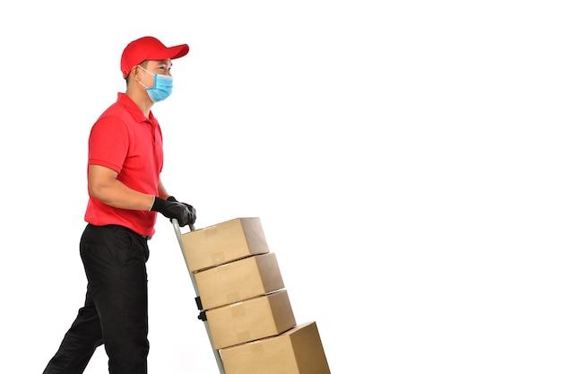 Gelukkige jonge aziatische leveringsmens in rood uniform, medisch gezichtsmasker, beschermende handschoenen die een steekwagen met geïsoleerde dozen duwen
