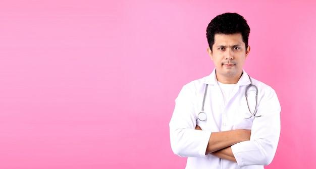 Gelukkige jonge aziatische man arts op een roze achtergrond in de studio