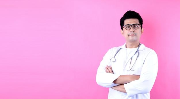 Gelukkige jonge aziatische man arts op een roze achtergrond