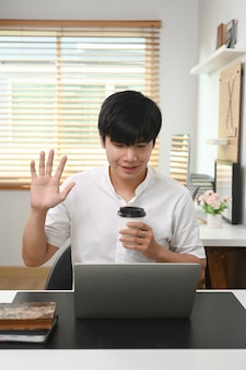 Gelukkige jonge aziatische man die een koffiekopje vasthoudt en zijn vrienden begroet tijdens een videogesprek op een laptopcomputer.