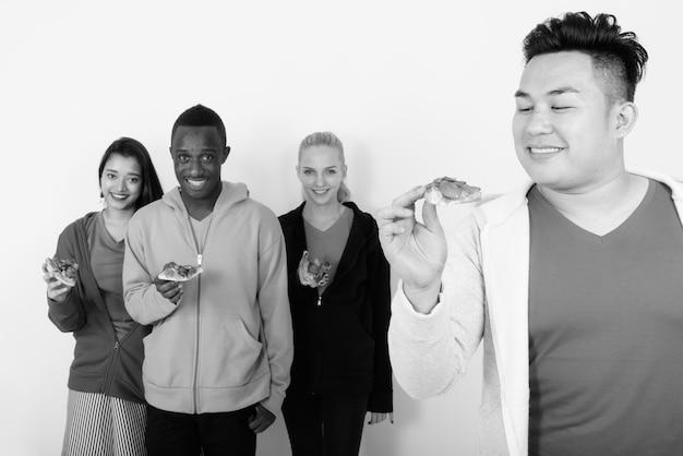 Gelukkige jonge aziatische man die naar een stuk pizza kijkt met een diverse groep multi-etnische vrienden die glimlachen en een stuk pizza bij elkaar houden