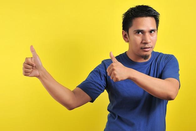 Gelukkige jonge aziatische man die twee duimen opgeeft, geïsoleerd op lichtoranje achtergrond