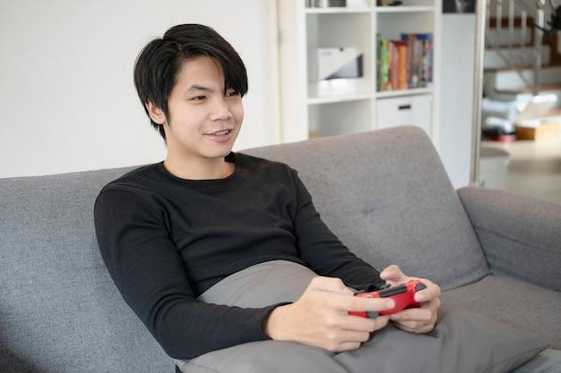 Gelukkige jonge aziatische man die videogame speelt met joystick op de bank.