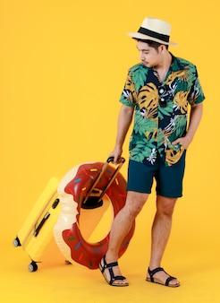 Gelukkige jonge aziatische man met kleurrijk gedrukt hawaiiaans shirt en panamahoed trekt gele koffer en zwemring. full body studio portret op gele achtergrond. zomer vakantie reizen concept.