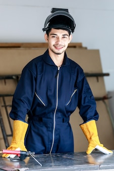 Gelukkige jonge aziatische mannelijke lasser in donkerblauwe overalls die achter de werktafel staan. workshop en bouw veiligheidsconcept.
