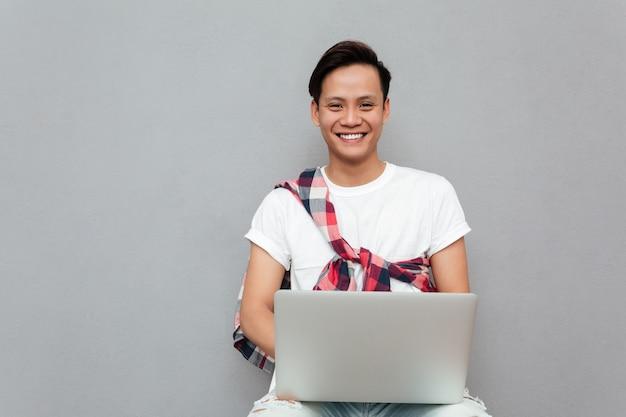 Gelukkige jonge aziatische mens die laptop met behulp van