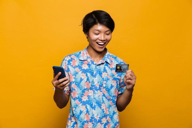 Gelukkige jonge aziatische mens die zich geïsoleerd over gele ruimte bevindt die de creditcard van de mobiele telefoonholding met behulp van.