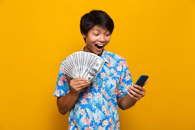 Gelukkige jonge aziatische mens die zich geïsoleerd over gele ruimte bevindt die geld houdt en mobiele telefoon met behulp van.