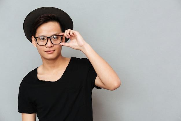 Gelukkige jonge aziatische mens status geïsoleerd over grijze muur