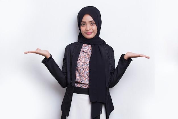 Gelukkige jonge aziatische moslimvrouw die met vingers naar verschillende richtingen wijst die op wit worden geïsoleerd