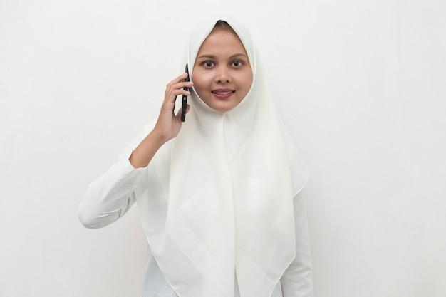 Gelukkige jonge aziatische moslimvrouw die mobiele telefoon met behulp van