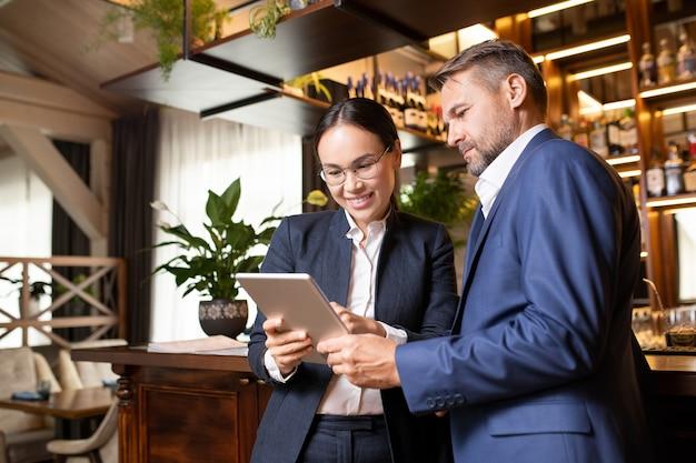 Gelukkige jonge aziatische onderneemster die presentatie aan haar partner maakt terwijl beide zich door toog in restaurant bevinden