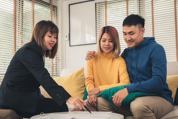 Gelukkige jonge aziatische paar en makelaar in onroerend goed