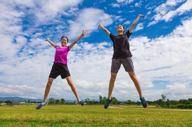 Gelukkige jonge aziatische tieners die voor vreugde openlucht op heldere zonnige dag springen
