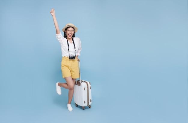Gelukkige jonge aziatische toeristenvrouw die bagage houdt die op vakantie gaat reizen die op blauwe achtergrond wordt geïsoleerd.