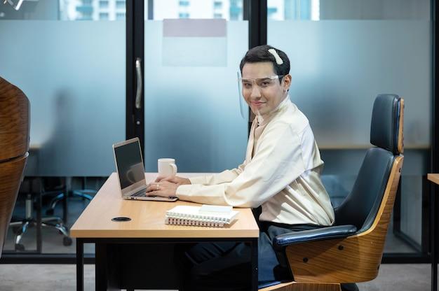 Gelukkige jonge aziatische travestietbeambte die met laptop en document aan bureau in het bureau werken