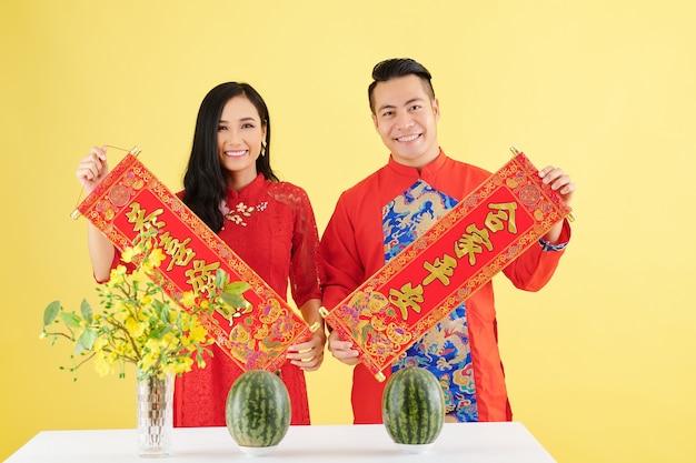 Gelukkige jonge aziatische vriend en vriendin in traditionele jurken met wanddecoraties voor het nieuwe maanjaar met de beste wensen inscriptie aan de eettafel