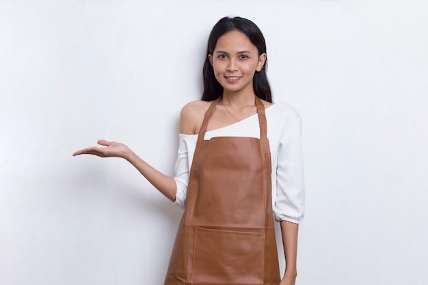 Gelukkige jonge aziatische vrouw barista serveerster wijzend met vingers naar verschillende richtingen