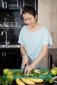 Gelukkige jonge aziatische vrouw die aan de balie staat en selderij snijdt terwijl ze groene smoothie maakt