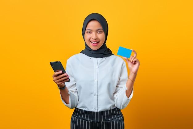 Gelukkige jonge aziatische vrouw die creditcard en mobiele telefoon bij de hand op gele achtergrond toont