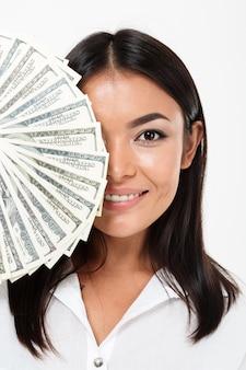 Gelukkige jonge aziatische vrouw die gezicht behandelt met geld.