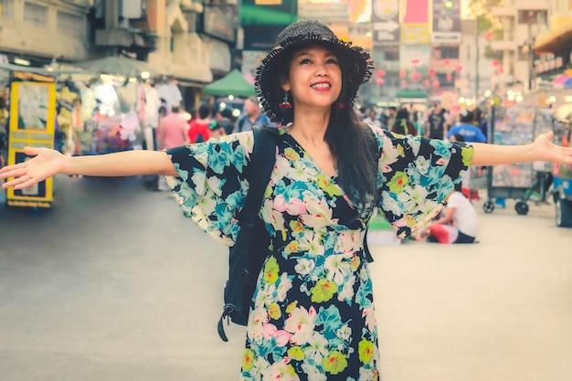 Gelukkige jonge aziatische vrouw die haar vakantie in khao san-weg doorbrengt, is khao san-weg toeristenknooppunt van bangkok.
