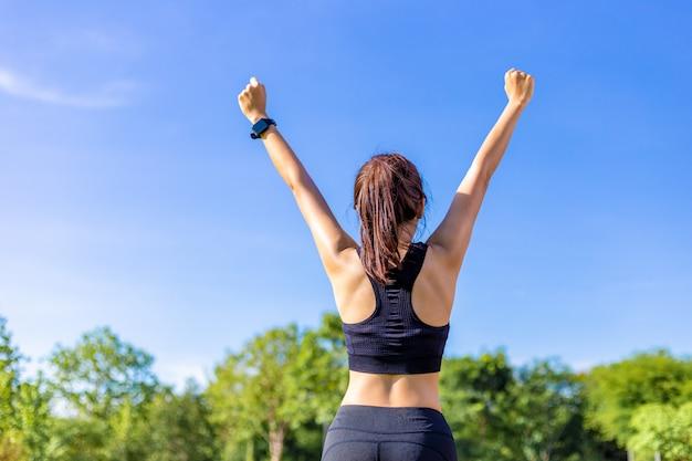 Gelukkige jonge aziatische vrouw die haar wapens vrolijk opheft na voltooi haar oefeningsroutine bij een openluchtpark op een heldere zonnige dag