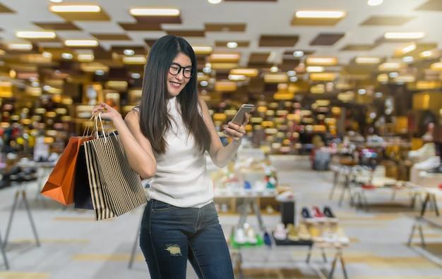 Gelukkige jonge aziatische vrouw die in gelukkig gevoel winkelt en de productdocument zak houdt