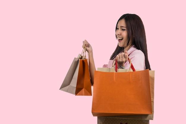 Gelukkige jonge aziatische vrouw die in gelukkig gevoel winkelt en de productdocument zak op pastellood houdt