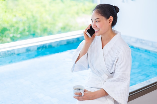 Gelukkige jonge aziatische vrouw die in witte badjas een kop hete koffie houdt om te drinken