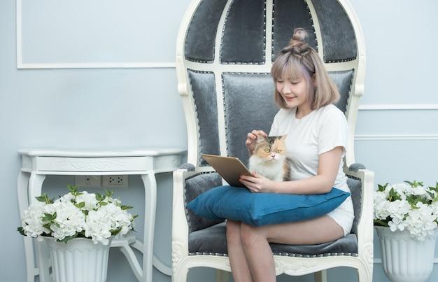 Gelukkige jonge aziatische vrouw die met tabletcomputer in haar handen katjeszitting op bank aaien