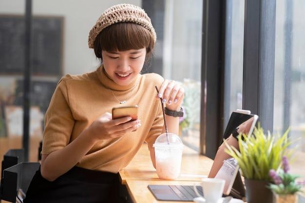 Gelukkige jonge aziatische vrouw die mobiele telefoon gebruikt
