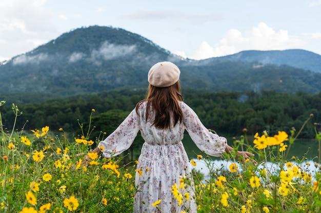 Gelukkige jonge aziatische vrouw die op geel bloemgebied bij zonsondergang genieten van.