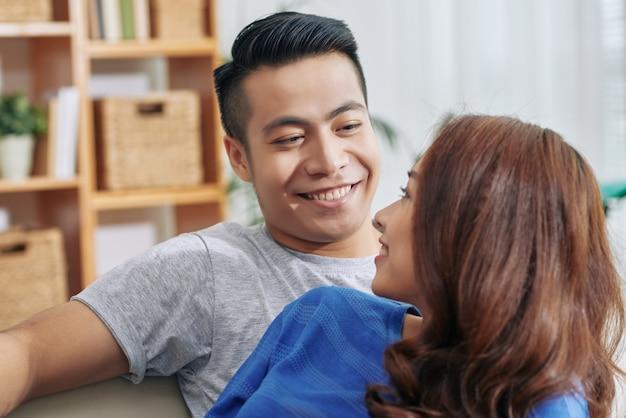Gelukkige jonge aziatische vrouw die over schouder knappe echtgenoot thuis bekijken
