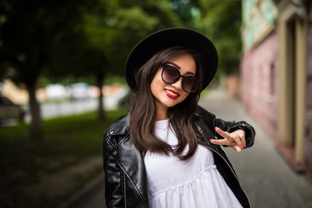Gelukkige jonge aziatische vrouw die selfie met vredesteken nemen op stadsstraat.