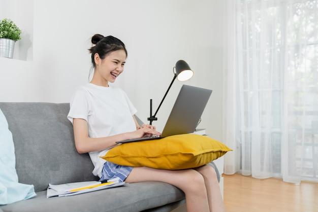 Gelukkige jonge aziatische vrouw die voor laptop met grafiekdocumenten werken van huis aan de bank, en online concept samenkomen opleiden.