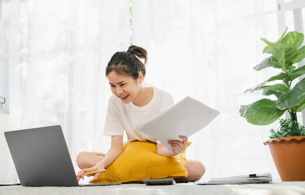 Gelukkige jonge aziatische vrouw die voor laptop met grafiekdocumenten werken van huis aan het tapijt, en online concept samenkomen opleiden.