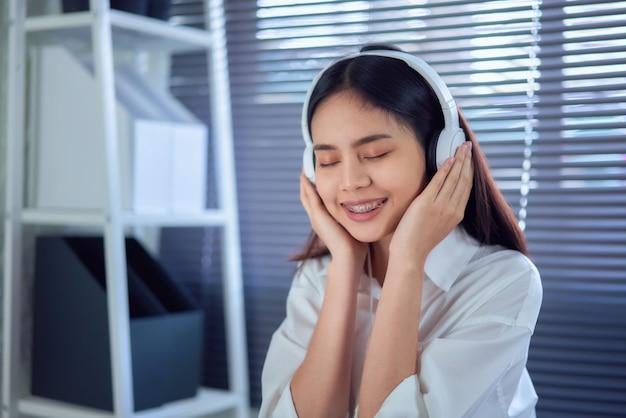 Gelukkige jonge aziatische vrouw die witte hoofdtelefoons draagt die van muziek luisteren te houden bij de lijst aangaande huisbureau.