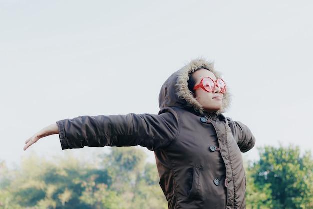 Gelukkige jonge aziatische vrouw met grote rode zonnebril