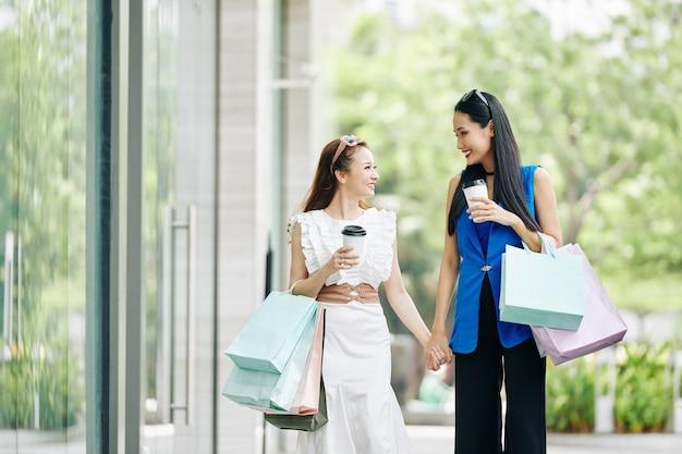 Gelukkige jonge aziatische vrouwen die koffie drinken en naar elkaar kijken tijdens het buiten wandelen na het winkelen