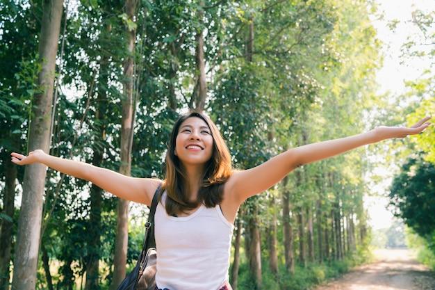 Gelukkige jonge aziatische vrouwenreiziger die met rugzak in bos lopen.