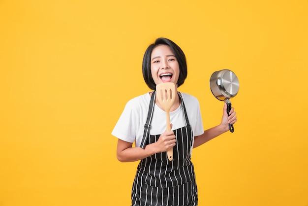 Gelukkige jonge aziatische vrouwenslijtage op een schort en handen die spatel met pot op lichtoranje muur tonen