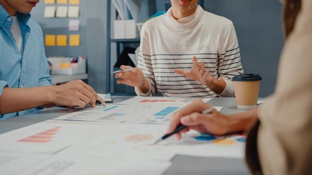 Gelukkige jonge aziatische zakenlieden en onderneemsterbijeenkomst brainstormen over enkele nieuwe ideeën over project