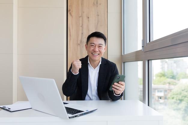 Gelukkige jonge aziatische zakenman op kantoor die naar de camera kijkt met emoties van de winnaar