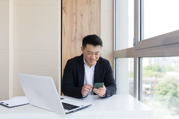 Gelukkige jonge aziatische zakenman op kantoor die naar mobiele telefoon kijkt