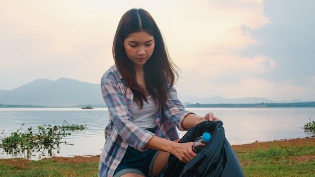 Gelukkige jonge azië-activisten die plastic afval op het strand verzamelen. koreaanse vrouwelijke vrijwilligers helpen de natuur schoon te houden en vuilnis op te halen. concept over milieuvervuiling problemen.
